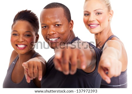 smiling group of gym instructors pointing at the camera on white background - stock photo