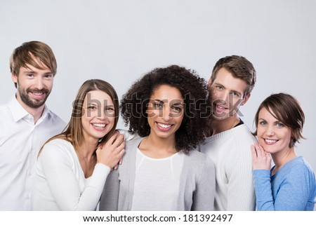 Smiling group of happy young friends posing together grouped around an attractive African American woman - stock photo