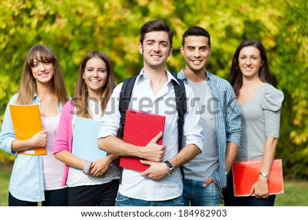 Smiling group of students at the park - stock photo