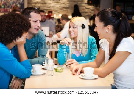 smiling   group of students taking a break from their studies in cafe - stock photo