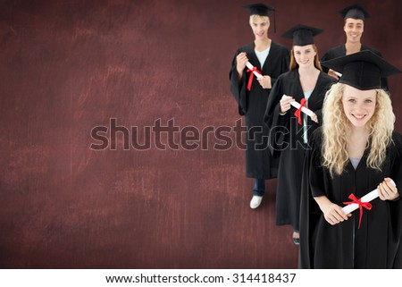Smiling group of teenagers celebrating after Graduation against desk - stock photo