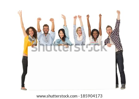 Smiling group of young friends showing large poster and cheering on white background - stock photo