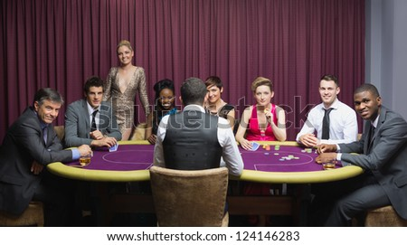 Smiling group sitting around poker table in casino - stock photo