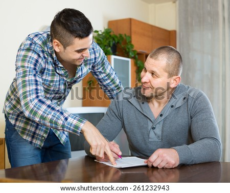 Smiling guy explains to his friend to fill banking document at home - stock photo