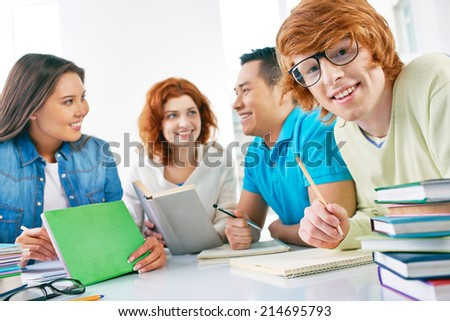 Smiling guy in eyeglasses looking at camera with his groupmates on background - stock photo