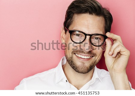 Smiling guy in glasses against pink background - stock photo