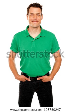 Smiling guy posing with hands in jeans pocket standing against white - stock photo