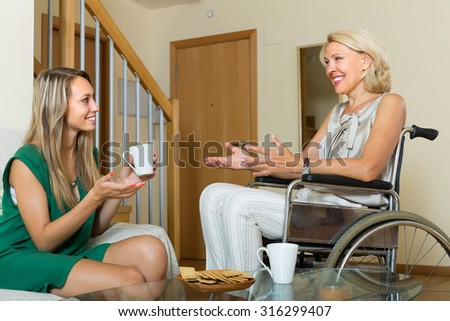 Smiling handicapped woman talking with female guest at the table - stock photo
