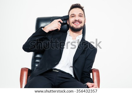 Smiling handsome bearded business man in black suit and white shirt sitting in office chair with gun at his temple over white background - stock photo