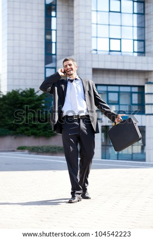 Smiling handsome business man on the phone outside his office - stock photo