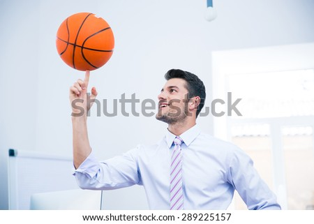 Smiling handsome businessman spining ball in office - stock photo