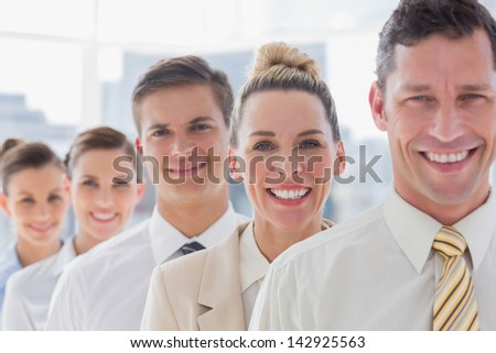 Smiling handsome businessman standing with his team in the office - stock photo