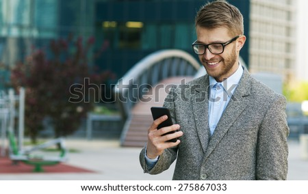 Smiling handsome businessman uses smart phone - stock photo