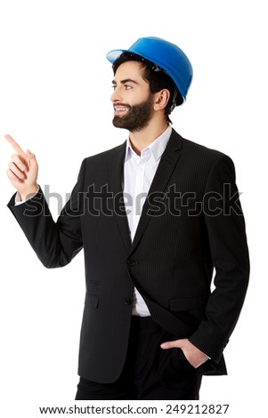 Smiling handsome businessman with hard hat pointing up. - stock photo