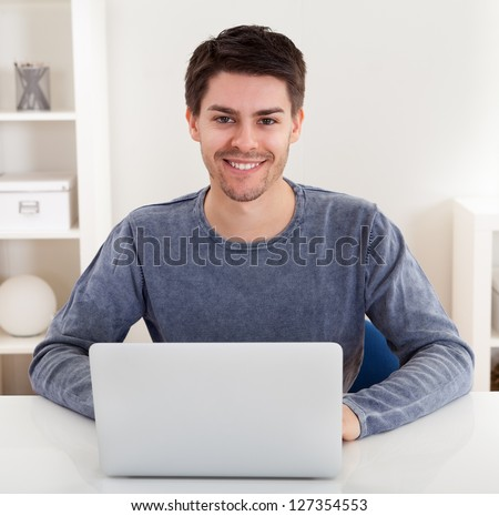 Smiling handsome casual young man sitting at a table using a laptop in a home office - stock photo