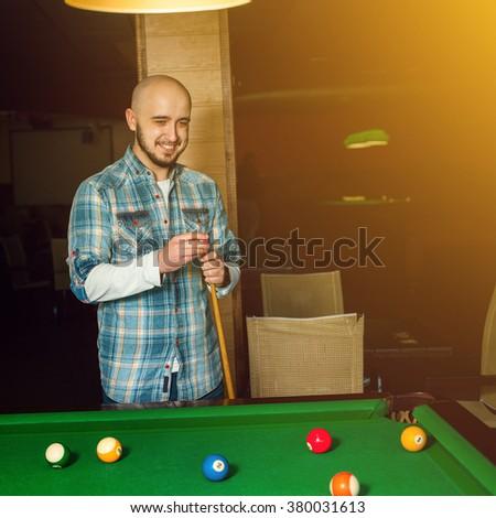 smiling handsome guy rubs cue chalk. Billiard sport concept. American pool billiard. Pool billiard game. - stock photo