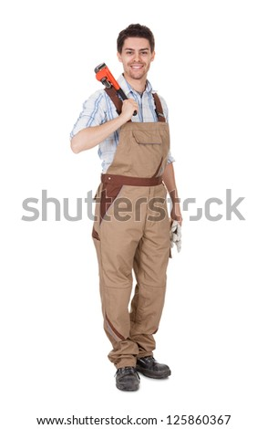 Smiling handsome handyman in work clothes with tool - stock photo