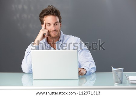 Smiling handsome male office worker sitting at desk looking at laptop computer screen. - stock photo