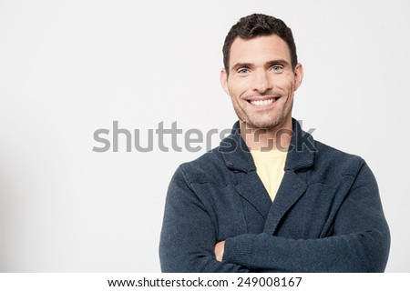 Smiling handsome male with crossed arms - stock photo