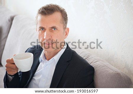 Smiling handsome man holding a cup of tea sitting on the sofa - stock photo