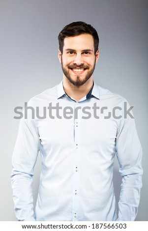 smiling handsome man in blue shirt, on grey background - stock photo