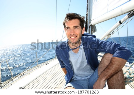 Smiling handsome man on sailboat - stock photo