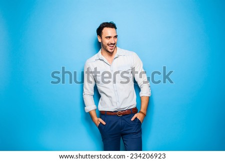 smiling handsome man with hands in pockets looking in one direction on blue background - stock photo