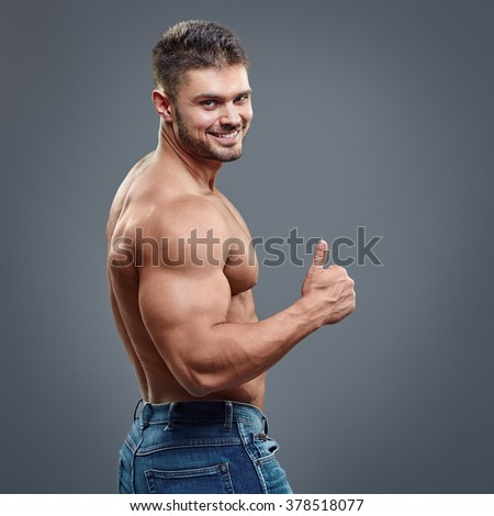 Smiling handsome man with muscular torso shows thumbs up sign - isolated on grey background. - stock photo