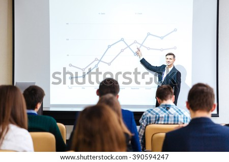 Smiling handsome speaker standing and explaining graphs on business conference in meeting hall - stock photo