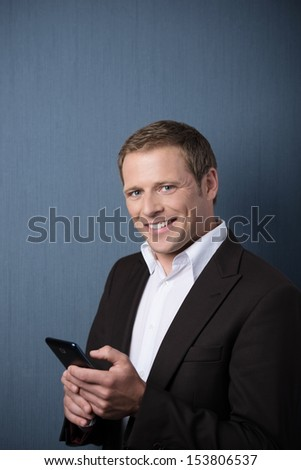 Smiling handsome young business man with a mobile phone in his hands standing looking sideways at the camera against a blue background - stock photo