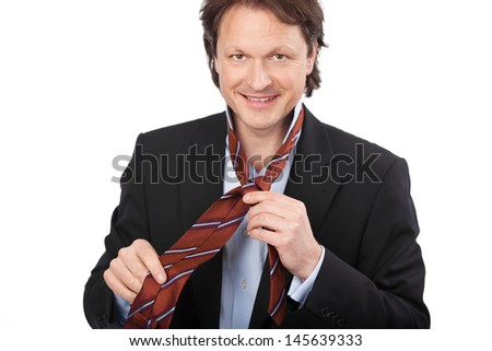 Smiling handsome young businessman tying his tie isolated on white - stock photo