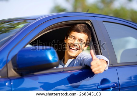 Smiling handsome young driver showing thumb up through open car window - stock photo