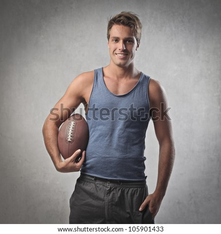 Smiling handsome young man holding a rugby football - stock photo