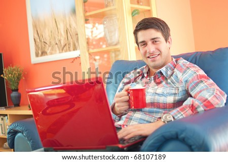 Smiling handsome young man holding cup of coffee and working on laptop computer at home - stock photo