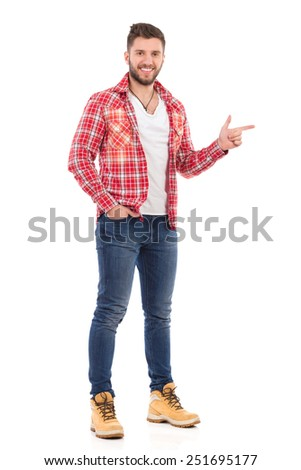 Smiling handsome young man in jeans and lumberjack shirt standing and pointing. Full length studio shot isolated on white. - stock photo