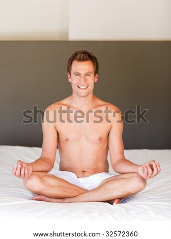 Smiling handsome young man meditating on bed - stock photo