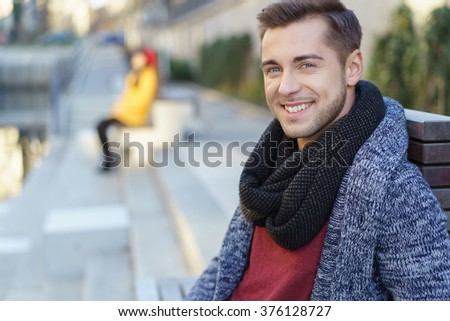 Smiling handsome young man outdoors in the city sitting relaxing overlooking a canal smiling at the camera, close up view - stock photo