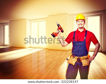 smiling handyman with drill in house - stock photo