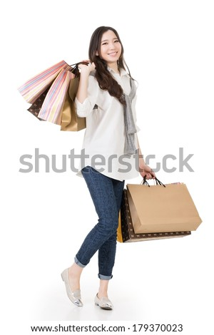 Smiling happy Asian woman shopping and holding bags, full length portrait isolated on white background. - stock photo