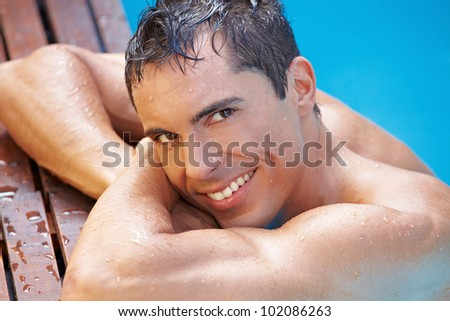Smiling happy attractive man in swimming pool with blue water - stock photo