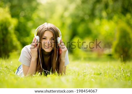 Smiling happy attractive teenager enjoying her music lying on her stomach on the grass in a leafy green park listening to tunes on her headphones, with copyspace - stock photo