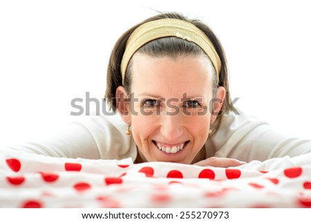 Smiling happy attractive woman lying on a colorful red polka dot counterpane on a bed facing the camera with a friendly warm smile. - stock photo
