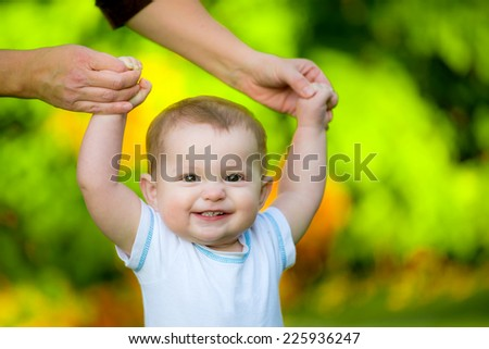 Smiling happy baby learning to walk outdoors - stock photo
