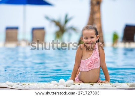 Smiling happy beautiful girl having fun in outdoor swimming pool - stock photo