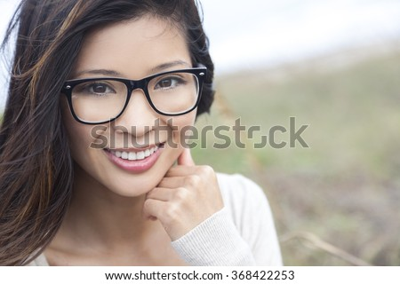 Smiling happy beautiful young Asian Chinese woman or girl wearing geek glasses outside - stock photo