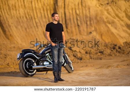 Smiling happy biker in sitting unknown on big chopper bike on road - stock photo