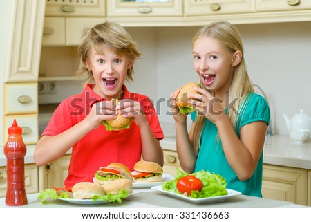 smiling happy boy and girl eating hamburgers or sandwiches - stock photo