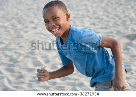 smiling happy boy has fun running at the beach, playing in sand - stock photo