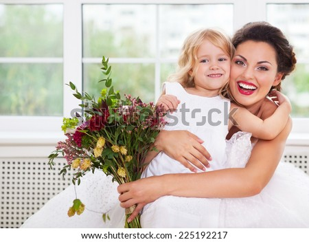 Smiling happy bride and a flower girl indoors. Horizontal shot - stock photo