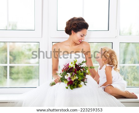 Smiling happy bride and a flower indoors. Horizontal shot - stock photo